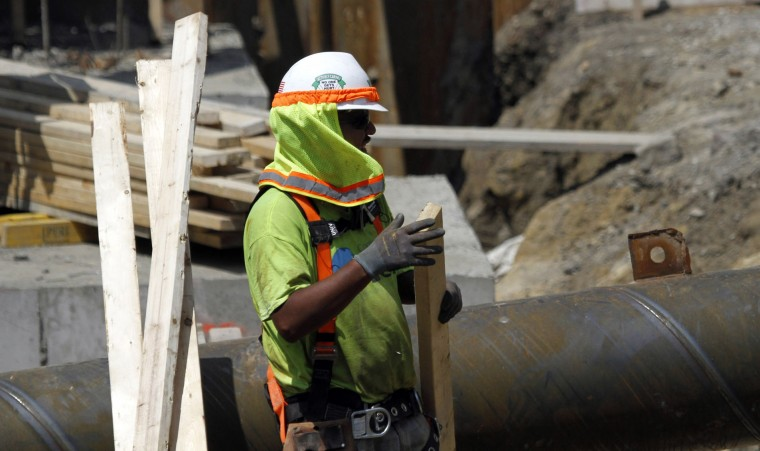A construction worker handles lumber at a luxury apartment site, Wednesday, July 20, 2016, in Chicago. The Occupational Safety and Health Administration urged employers to protect laborers doing construction, road and agricultural work, as high temperatures and humidity will affect the central United States this week, sending heat indexes as high as 115 degrees in some places for the first time this year. (AP Photo/Tae-Gyun Kim)