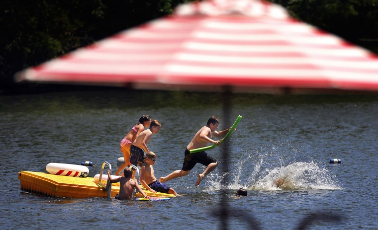 "Kids leap into Keen Lake on Thursday, July 21, 2016, in Canaan Township, Pa. The high pressure system, sometimes called a ""heat dome,"" will push conditions to their hottest point so far this summer, though record hot temperatures are not expected, according to the National Weather Service. (Butch Comegys/The Times & Tribune via AP)"
