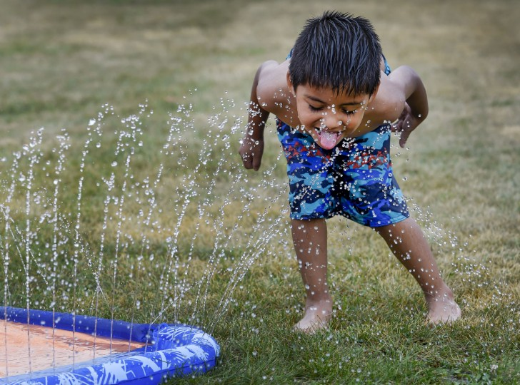 Leonardo Bucio, 5, tries to get a drink of water Thursday morning, July 21, 2016, as children in the St. Edwards Child Development Center's School Age Summer Camp in Racine, Wis., play in the water. The children were playing in the water to keep cool after their scheduled field trip was canceled due to the excessive heat warning issued by the National Weather Service. (Gregory Shaver/The Journal Times via AP)