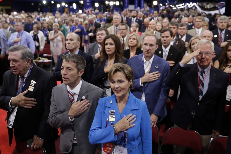 Alabama delegate Judy Carns, center in blue, and other delegates put their hands on their chests as they sing the national anthem during first day of the Republican National Convention in Cleveland, Monday, July 18, 2016. (AP Photo/Matt Rourke)