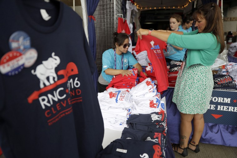 A woman checks out a tee shirt at a merchandise booth outside Quicken Loans Arena during first day of the Republican National Convention in Cleveland, Monday, July 18, 2016. (AP Photo/Matt Rourke)
