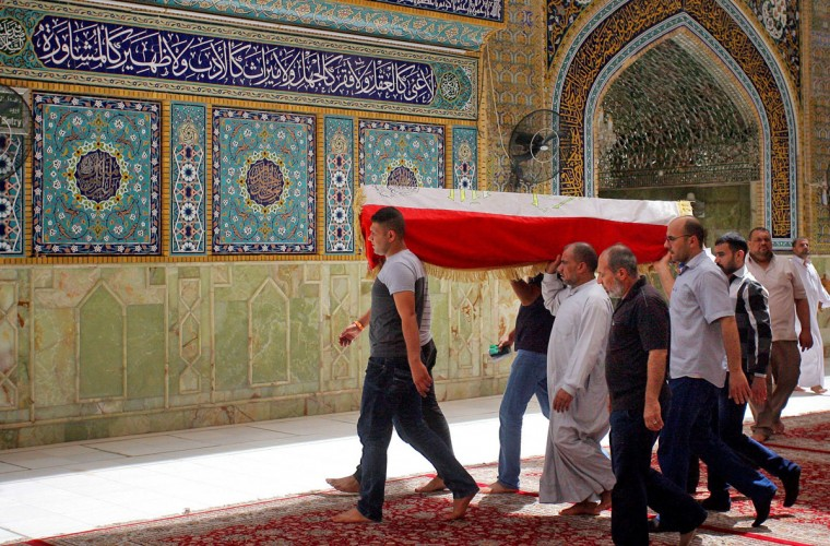 Mourners carry the Iraqi flag-draped coffin of Hamza Jabbar, 37, who was killed from a bomb attack in Karada neighborhood, during his funeral procession at the holy shrine of Imam Ali in Najaf, 100 miles (160 kilometers) south of Baghdad, Iraq, Sunday, July 3, 2016. Dozens of people have been killed and more than 100 wounded in two separate bomb attacks in the Iraqi capital Sunday morning, Iraqi officials said. (AP Photo/Anmar Khalil)