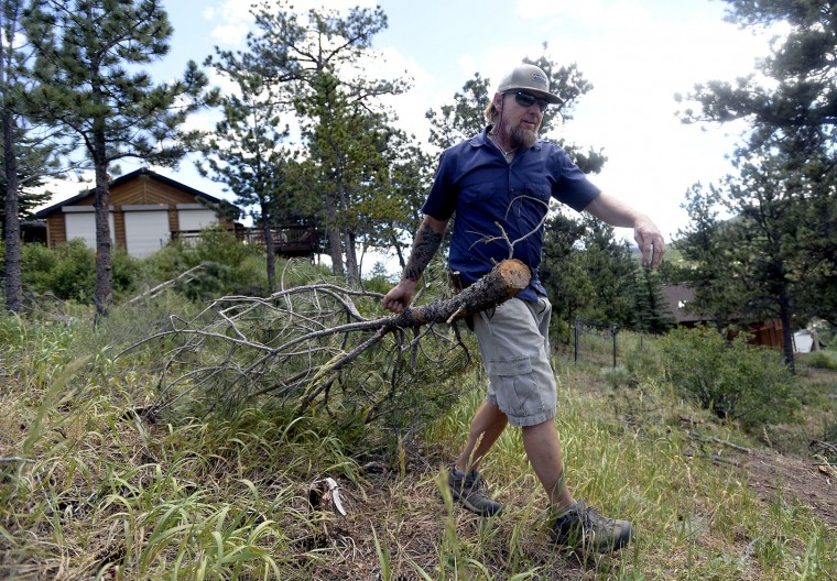 Duane Blankenship works to mitigate fire hazards from his home on the Peak to Peak highway near Ridge Road while crews battle the Cold Springs Wildfire on Monday near Nederland, Colo. on Monday, July 11, 2016, near Nederland, Colo. (Jeremy Papasso/Daily Camera via AP)
