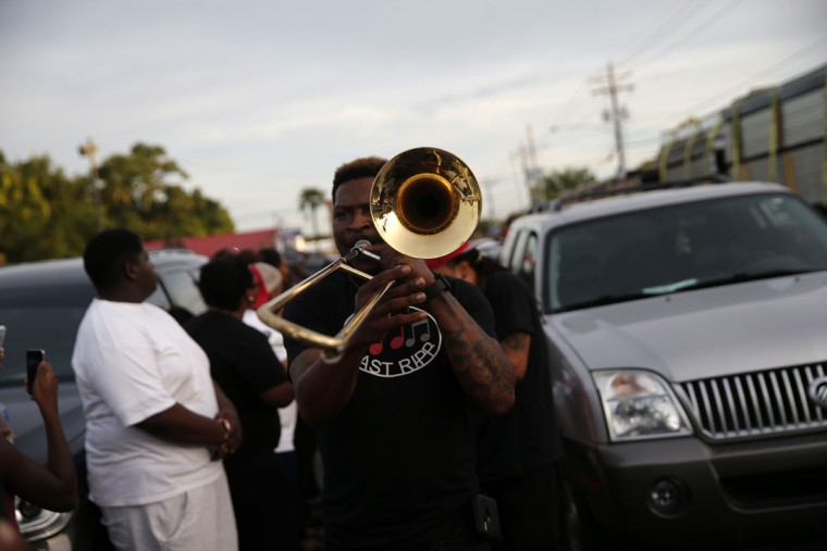A brass band marches through the street after a vigil for Alton Sterling, who was shot and killed during a scuffle with police officers, outside the Triple S convenience store in Baton Rouge, La., Wednesday, July 6, 2016. In a swift move by authorities to keep tensions from boiling over, the U.S. Justice Department launched a civil rights investigation Wednesday into the video-recorded killing of Sterling, who was shot as he scuffled with two white police officers on the pavement outside the convenience store. (AP Photo/Gerald Herbert)