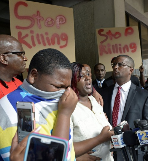 Cameron Sterling, left, Alton Sterling's son, cries, as his mother Quinyetta McMillan speaks about the shooting of Alton Sterling during a press conference and protest at city hall Wednesday, July 6, 2016. Alton Sterling was shot and killed by a Baton Rouge police officer Tuesday outside a store where he was selling CDs. (Bill Feig/The Advocate via AP)