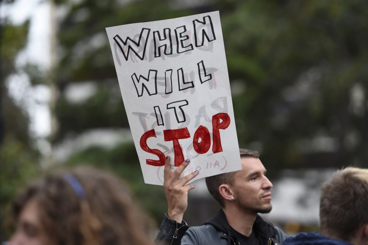 In this photo taken Thursday, July 7, 2016, a demonstrator holds a sign at Frank H. Ogawa Plaza during a protest in Oakland, Calif., protesting deadly police shootings of black men. The protest began with a mostly peaceful rally and march. Officer Johnna Watson says in a news release that about 1,000 demonstrators then headed to Interstate 880, bringing traffic to a halt. (Jose Carlos Fajardo/San Jose Mercury News via AP)
