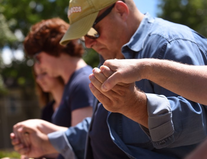 Jim Constantine, right, his wife Gretchen Constantine, left, and others joined hands during a prayer service for local police, and those police officers who were fatally shot during what began as a peaceful protest in Dallas, Friday afternoon, July 8 2016, at Memorial Park in Arlington Heights, Ill. (Jeff Knox/Daily Herald via AP)