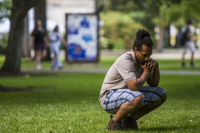 In this photo taken Thursday, July 7, 2016, Eric Aiken stares at the ground as he listens to speakers during a vigil at the University of Michigan Diag in Ann Arbor, Mich., in honor of Alton Sterling and Philando Castile, two black men recently shot and killed by police. (Katy Kildee/The Ann Arbor News via AP)