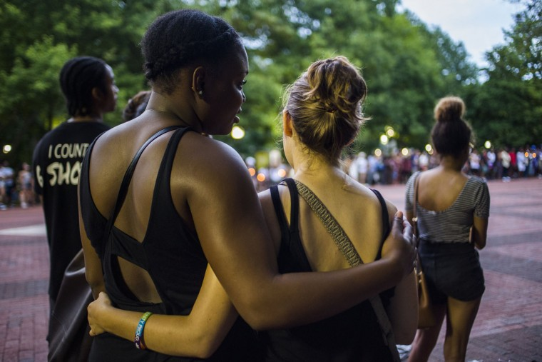 In this photo taken Thursday, July 7, 2016, two women stand together during a vigil at the University of Michigan Diag in Ann Arbor, Mich., in honor of Alton Sterling and Philando Castile, two black men recently shot and killed by police. (Katy Kildee/The Ann Arbor News via AP)