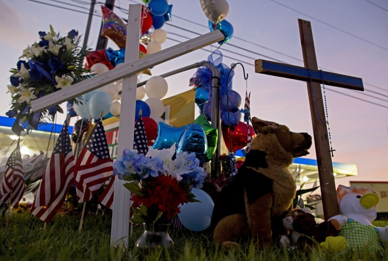 A makeshift memorial sits in front of the B-Quick convenience store Tuesday, July 19, 2016, in Baton Rouge, La., after law enforcement officers were killed on Sunday. A former Marine set out to ambush police in Baton Rouge, authorities said Monday. (AP Photo/Max Becherer)