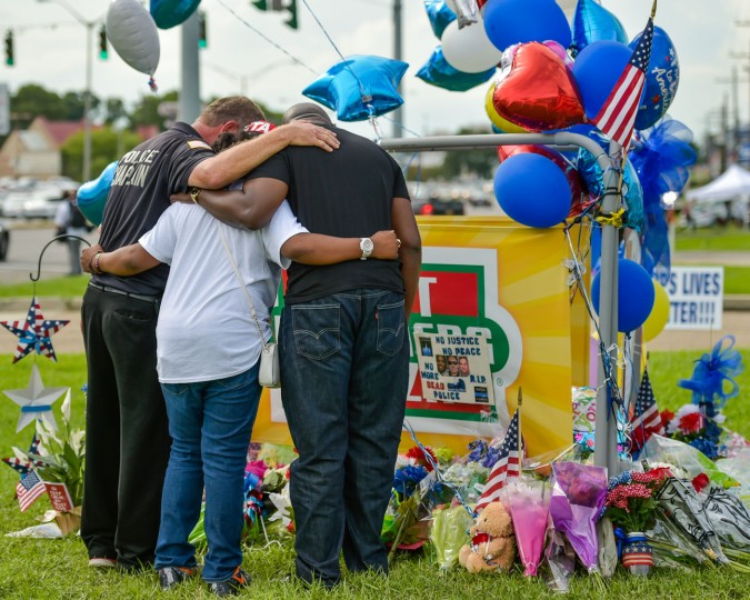 People gather around a memorial at the location where Baton Rouge police officers were killed and wounded, Monday, July 18, 2016, in Baton Rouge, La. (Scott Clause/The Daily Advertiser via AP)