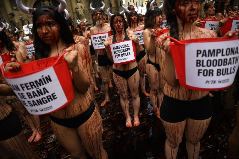 People cover their bodies with theatrical blood as they hold buckets with slogans to protest against bull runs in front of the City Hall on the eve of the famous San Fermin festival, in Pamplona, northern Spain, Tuesday, July 5, 2016. The festival will begin on July 6 with the ''txupinazo'' opening ceremony, with people participating in bull runs, music and dance, through the old city. (AP Photo/Alvaro Barrientos)