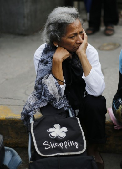 In this Friday, July 8, 2016 photo, a woman waits in line outside a supermarket to buy food in Caracas, Venezuela. Shortages now top voters lists of concerns, surpassing even safety. That's stunning in a country with one of the world's highest murder rates. (AP Photo/Ariana Cubillos)