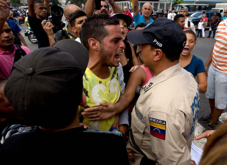 """In this Wednesday, June 8, 2016 file photo, a man waiting in line at a grocery store argues with a Bolivarian National Police officer as he and others wait for food to arrive to the store in Caracas, Venezuela. """"As the economy breaks down, life is telescoping to be just lines,"""" said Datanalisis president Luis Vicente Leon. """"You have masses of people in the streets competing for scarce goods. You're inevitably going to get conflict, fights, tricks, you name it."""" (AP Photo/Fernando Llano, File)"""