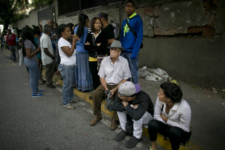 In this Monday, July 4, 2016 photo, people wait in line to buy food outside a supermarket in Caracas, Venezuela. The extent of the country's economic collapse can be measured in the length of the lines snaking through every neighborhood. (AP Photo/Ariana Cubillos)