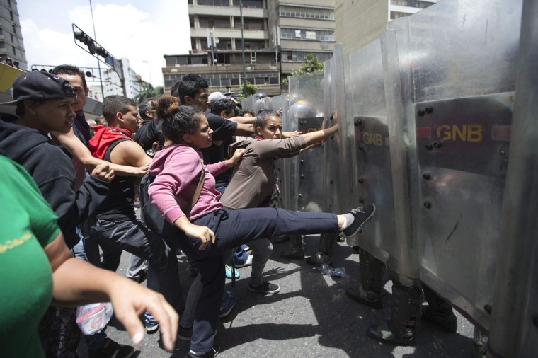 In this Thursday, June 2, 2016 photo, a woman kicks the shield of a National Guard soldier as other demonstrators push during a food protest a few blocks from Miraflores presidential palace in Caracas, Venezuela. Clashes broke out after people waiting for hours at a nearby grocery store learned a food supply truck was turned away. The shoppers got as close to the presidential palace as they could, and were joined by other demonstrators. (AP Photo/Ariana Cubillos, File)