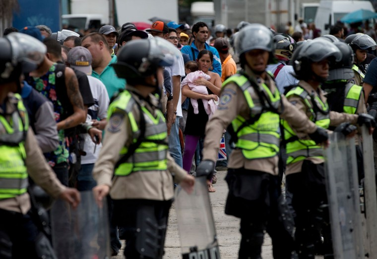 In this June 1, 2016 file photo, a woman holding a baby looks at police in riot gear standing guard as she and others wait outside a supermarket to buy food in Caracas, Venezuela. As Venezuela's lines have grown longer and more dangerous, they have become not only the stage for everyday life, but a backdrop to death. More than two dozen people have been killed in line in the past 12 months. (AP Photo/Fernando Llano, File)