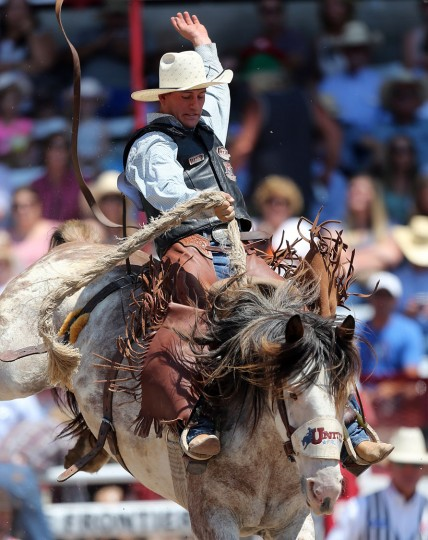 Charlie Kogianes of Provo, Utah, competes in the saddle bronc event during the fifth day of the 120th annual Cheyenne Frontier Days Rodeo Wednesday afternoon, July 27, 2016, at Frontier Park Arena in Cheyenne, Wyo. (Blaine McCartney/Wyoming Tribune Eagle via AP)