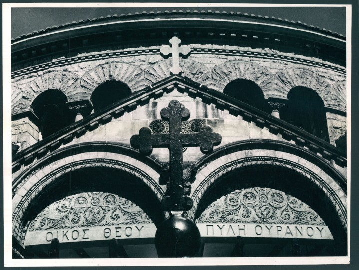 "April 25, 1963 - THIS IS BALTIMORE -- The facade of the Greek Orthodox Church, ""Evangelismos,"" located at Maryland Avenue and Preston Street, stands as a symbol of a Greek-American community in an ever-changing city. This unusual photograph brings together the cross on the church fence and the one on the building. ""The House of God is the Gate to Heaven"" is a translation of the inscription on the church. Photo by Robert F. Kniesche."