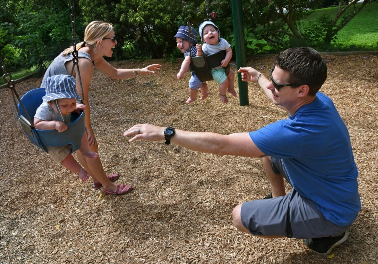 """Kristen and Thomas Hewitt Jr. enjoy swing time at a nearby playground in Hampden as much as their nine-month old triplets. Thomas """"Trip"""" Hewitt III is at left, and Oliver and Finnegan, known as """"Ollie"""" and """"Finn,"""" share the other swing. (Amy Davis, Baltimore Sun)"""
