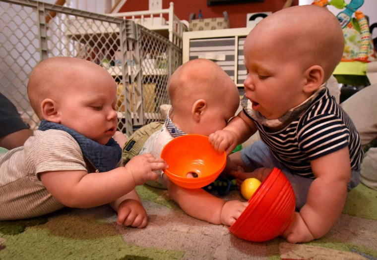 In a gentle tug-of-war, Ollie, right, pulls a toy away from Finn, left, as their brother Trip gets squeezed in the middle. (Amy Davis/Baltimore Sun)