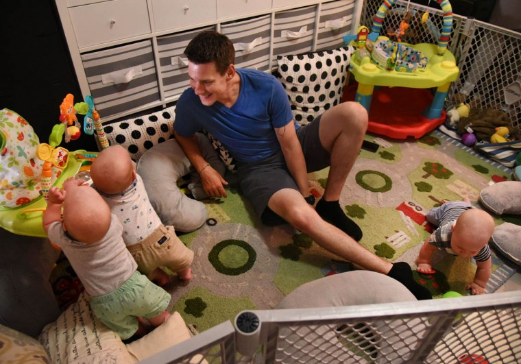 Thomas Hewitt Sr. watches Finn, left, and Trip pull themselves up as Ollie crawls at right. The fenced-in play area has pillows along the perimeter to give the triplets a soft landing when they fall. (Amy Davis/Baltimore Sun)