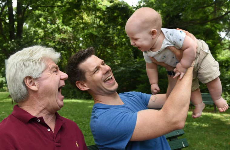 """Three generations share the same name: Thomas Hewitt Sr., left, of Ramsey, NJ, laughs with his grandson, Thomas """"Trip"""" Hewitt III, who is held aloft by Thomas Hewitt Jr. (Amy Davis/Baltimore Sun)"""