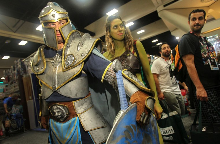 A foot soldier from the movie Warcraft guards the character Garona, center, during Comic-Con International 2016 in San Diego, California on July 21, 2016. (BILL WECHTER/AFP/Getty Images)
