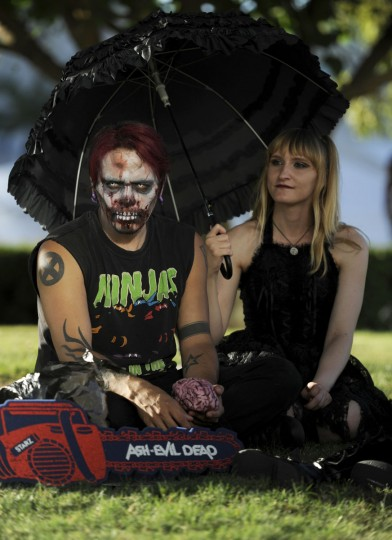 Eddie Quintero, left, and Nova Tepes of San Diego, sit under an umbrella outside on Day 1 of Comic Con International on Thursday, July 21, 2016, in San Diego. (Photo by Chris Pizzello/Invision/AP)