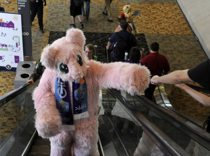"""Francis Magnanao of Flushing, New York, dresses as Fluffle Puff and gives a fan a fist bump. """"Its worth the travel,"""" Magnanao said. This is his third BronyCon convention. BronyCon is the world's largest My Little Pony: Friendship is Magic convention. Held at the Baltimore Convention Center, BronyCon features panels, meet-ups, activities, and cosplay. (Caitlin Faw/Baltimore Sun staff)"""