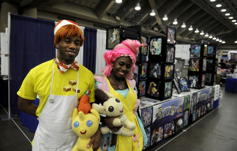 """Dantrell Bryant and Amiynah Bryant, dressed as Mr. and Mrs. Cake, pose for a picture in the Blank Canvas's Marketplace. The Bryants are from Atlanta, Georgia, and this is their second BronyCon. """"Loving it,"""" Amiynah said. BronyCon is the world's largest My Little Pony: Friendship is Magic convention. Held at the Baltimore Convention Center, BronyCon features panels, meet-ups, activities, and cosplay. (Caitlin Faw/Baltimore Sun staff)"""