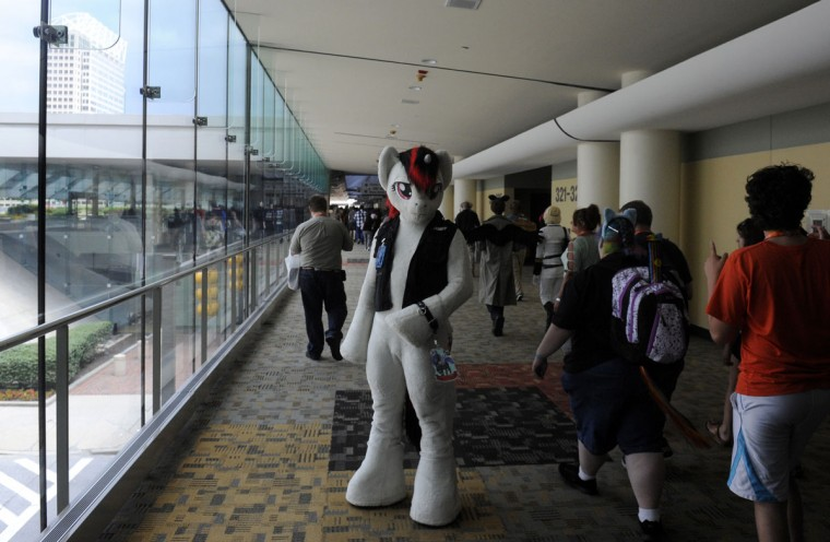 Security watches over the crowd at the Baltimore Convention Center. BronyCon is the world's largest My Little Pony: Friendship is Magic convention. BronyCon features panels, meet-ups, activities, and cosplay. (Caitlin Faw/Baltimore Sun staff)