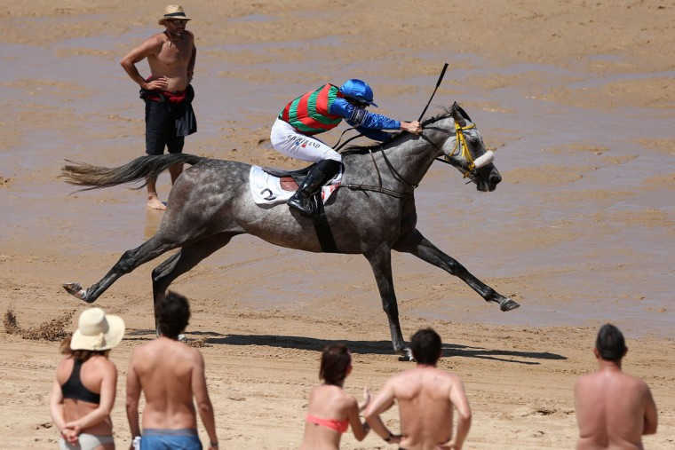 A jockey and his mount race along the beach during the annual beach horse race in Loredo, near the northern Spanish city of Santander, on July 24, 2016. (CESAR MANSO/AFP/Getty Images)