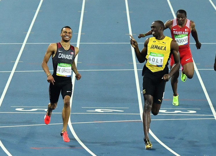 Jamaica's Usain Bolt (R) shares a laugh with de Canada's Andre De Grasse after winning his Men's 200m Semifinal during the athletics event at the Rio 2016 Olympic Games at the Olympic Stadium in Rio de Janeiro on August 17, 2016. (Jewel Samad/AFP/Getty Images)