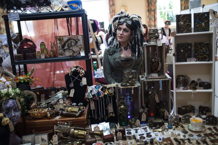 A stalholder stands behind her wares on the first day of 'The Asylum Steampunk Festival' in Lincoln, northern England on August 26, 2016. The four-day alternative lifestyle festival is the largest and longest running steampunk festival in the World; combining art, literature, music, fashion and comedy. Steampunk is a subgenre of science fiction or science fantasy that incorporates technology and aesthetic designs inspired by 19th-century industrial steam-powered machinery. / (AFP Photo/Oli Scarff)