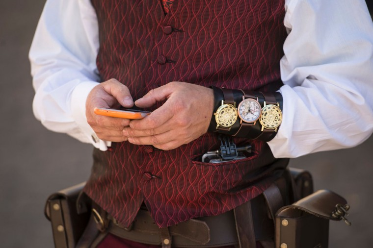 A Steampunk enthusiast uses a smartphone on the first day of 'The Asylum Steampunk Festival' in Lincoln, northern England on August 26, 2016. The four-day alternative lifestyle festival is the largest and longest running steampunk festival in the World; combining art, literature, music, fashion and comedy. Steampunk is a subgenre of science fiction or science fantasy that incorporates technology and aesthetic designs inspired by 19th-century industrial steam-powered machinery. / (AFP Photo/Oli Scarff)