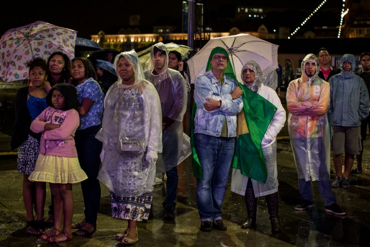 RIO DE JANEIRO, BRAZIL - AUGUST 21: People watch the Rio 2016 Olympics closing ceremony in the rain at the Olympic Boulevard live site on August 21, 2016 in Rio de Janeiro, Brazil. (Photo by Chris McGrath/Getty Images)
