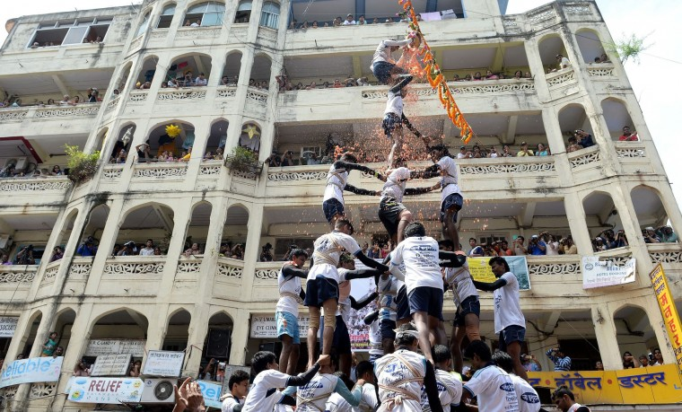 FILE - This file photograph taken on September 6, 2015 shows Indian Hindu devotees as they form a human pyramid in a bid to reach and break a dahi-handi (curd-pot) suspended in the air during celebrations for the Janmashtami festival, which marks the birth of Hindu God Lord Krishna in Mumbai. India's top court on August 17, 2016, has banned children from taking part in a popular but potentially dangerous religious festival in the country's west that sees young boys scale human pyramids. The Supreme Court barred children aged under 18 from scaling the pyramids and restricted their height to 20 feet (six metres) following a string of accidents in recent years. (Indranil Mukherjee/AFP/Getty Images)