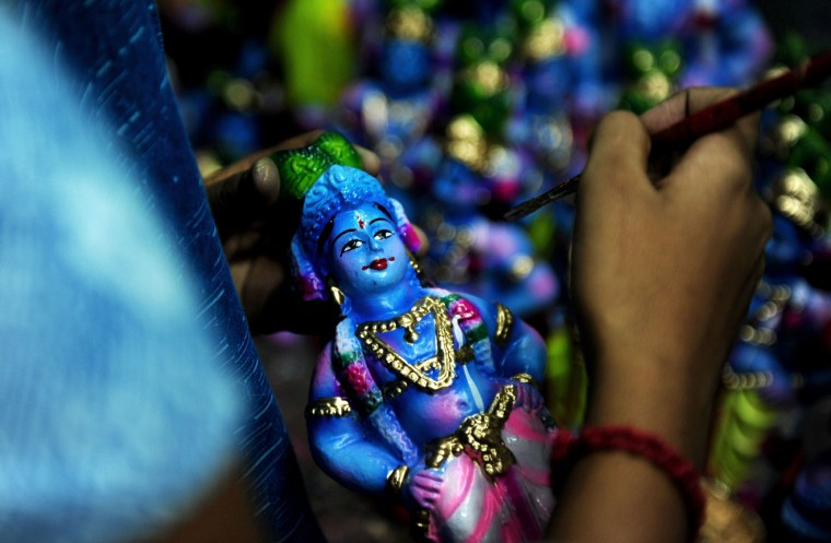 A Indian woman worker gives the finishing touches to an idol of Hindu god Krishna at a workshop on occasion of 'Krishna Janmashtami' in Chennai on August 20, 2016. The birthday of Indian Hindu God Krishna will be celebrated as 'Krishna Janmashtami' by Hindus all over world on August 25. (Arun Sankar/AFP/Getty Images)