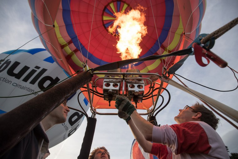 Pilot John Harris fires the burners as hot air balloons take to the skies at a preview flight to launch next week's Bristol International Balloon Fiesta on August 5, 2016 in Bristol, England. The four day event event, which will officially open next week on Thursday, is now in its 38th year and is Europe's largest annual hot air balloon event in the city that is seen as many as the home of modern ballooning. (Photo by Matt Cardy/Getty Images)