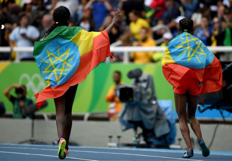 Ethiopia's Almaz Ayana (R) and Ethiopia's Tirunesh Dibaba wrapped in their national flag celebrate after they respectively won gold and bronze in the Women's 10,000m during the athletics event at the Rio 2016 Olympic Games at the Olympic Stadium in Rio de Janeiro on August 12, 2016. / (AFP Photo/Olivier Morin)