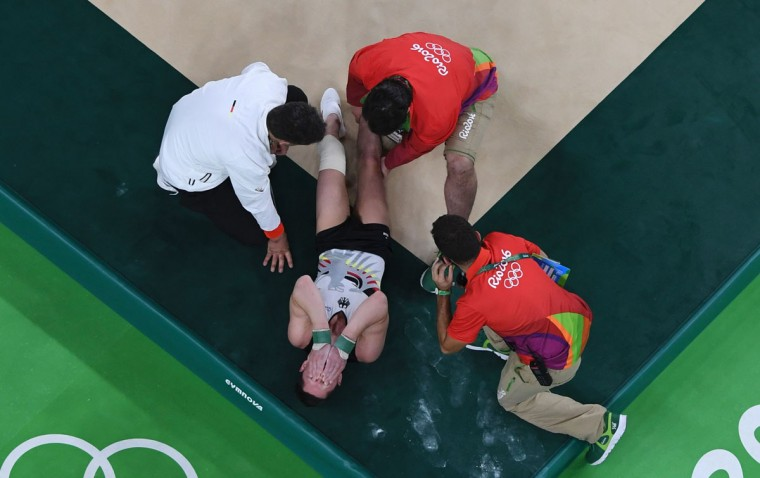 An overview shows Germany's Andreas Toba reacting after being injured while competing in the qualifying for the men's floor exercise event of the Artistic Gymnastics at the Olympic Arena during the Rio 2016 Olympic Games in Rio de Janeiro on August 6, 2016. (AFP PHOTO / Antonin THUILLIER)