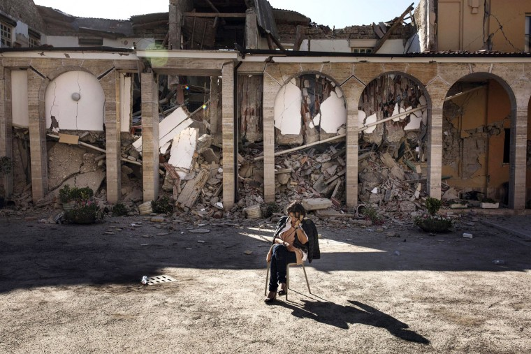 "A woman sits in the courtyard of the "" Don Minozzi "" convent in Amatrice, central Italy, Friday, Aug. 26, 2016, two days after an earthquake. Strong aftershocks damaged two key access roads into quake-struck Amatrice on Friday, threatening to isolate the tiny hilltop town as hopes dimmed that rescuers would find any more survivors from the earthquake that leveled three towns Wednesday. (Roberto Salomone/ANSA via AP)"