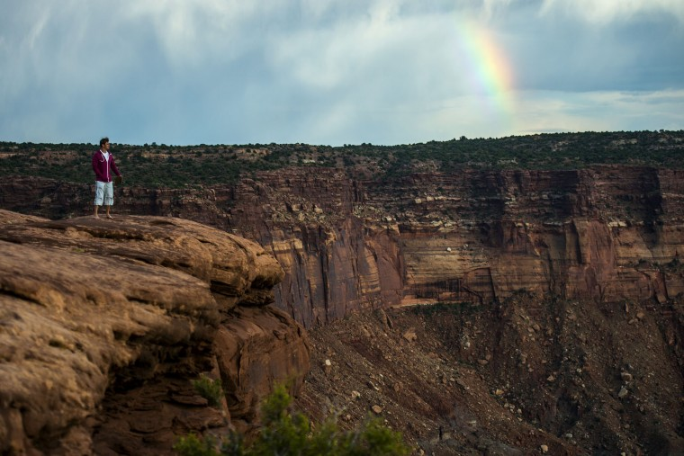 In this Wednesday, Aug. 24, 2016 photo, Roman Pontner, of Germany, looks at Canyonlands National Park from the Green River Overlook near Moab, Utah, as a rainbow appears in the background. The National Park Service marks its 100th anniversary on Thursday, Aug. 25, 2016. (Chris Detrick/The Salt Lake Tribune via AP)
