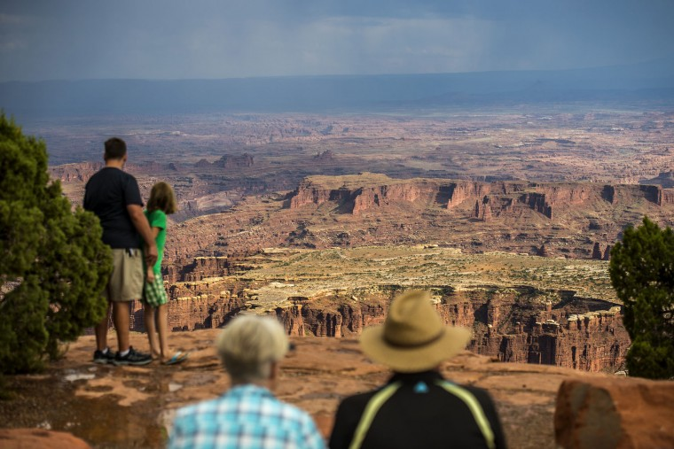 In this Wednesday, Aug. 24, 2016 photo, visitors look at Grand View Point in the Island in the Sky District at Canyonlands National Park near Moab, Utah. The National Park Service marks its 100th anniversary on Thursday, Aug. 25, 2016. (Chris Detrick/The Salt Lake Tribune via AP)