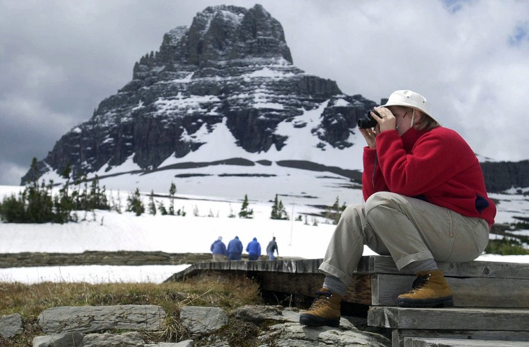 FILE - In this June 7, 2001, file photo, Brigitte Pentek, of Lewisburg, W.Va., uses binoculars to watch a gopher while waiting for her husband on one of the trails near Logan's Pass at Glacier National Park, Mont. With over 700 miles of trails, Glacier is a hiker's paradise for adventurous visitors seeking wilderness and solitude, according to the National Parks Service. (Mark Sterkel/The Great Falls Tribune via AP, File)