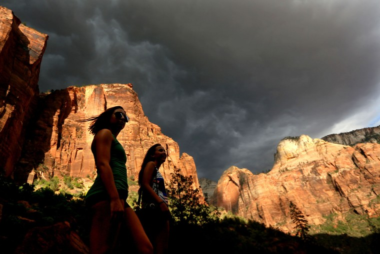 FILE - In this Monday, July 22, 2013, file photo, hikers look up at a fast moving storm as it makes its way through Zion National Park outside of Springdale, Utah. Both Zion and Bryce were formed millions of years ago when the Earth's crust violently heaved, leaving behind stunning, unique arrays of rock formations. (AP Photo/Sandy Huffaker, File)