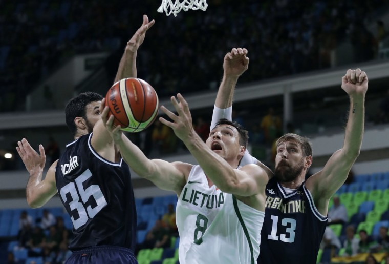 Lithuania's Jonas Maciulis (8) drives to the basket between Argentina's Roberto Acuna (35) and Andres Nocioni, right, during a basketball game at the 2016 Summer Olympics in Rio de Janeiro, Brazil, Thursday, Aug. 11, 2016. (AP Photo/Charlie Neibergall)