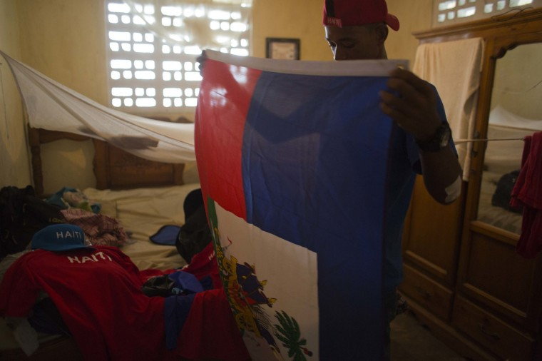 In this July 30, 2016 photo, Haitian Olympic swimmer Frantz Mike Itelord Dorsainvil folds a Haitian national flag to take with him as he packs for his trip to Rio de Janeiro, in the Port-au-Prince neighborhood Carrefour, Haiti. Dorsainvil says he's hopeful that the sport will take off in his Caribbean homeland if he and his teammate, 19-year-old Haitian-American Naomy Grand'Pierre, are able to win a medal. Grand'Pierre is a student at the University of Chicago and will be Haiti's first Olympic female swimmer. (AP Photo/Dieu Nalio Chery)