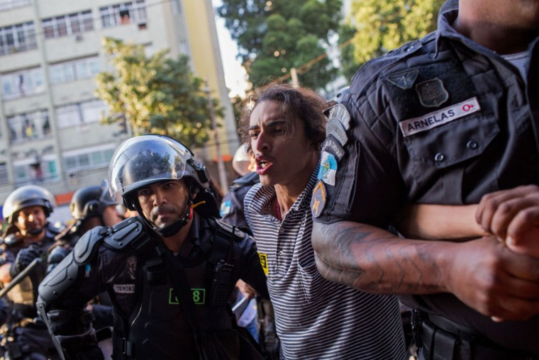 Police officers detain a man during a protest against the Rio's 2016 Summer Olympics near the Maracana stadium before the opening ceremony in Rio de Janeiro, Brazil, Friday, Aug. 5, 2016. (AP Photo/Mauro Pimentel)